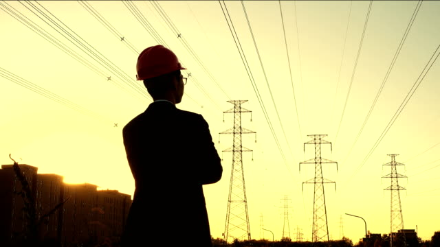 Electrical engineer rear view at sunset