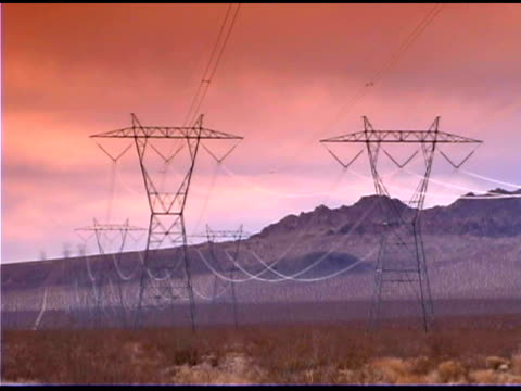 Electrical pylons in desert at dawn