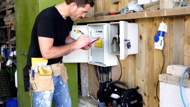 CRANE HD: Electrician inspecting Fuse box with Clipboard