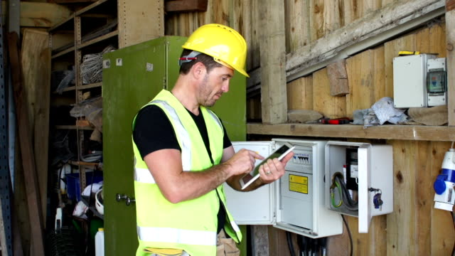 Electrician / Inspector with Digital Tablet at Fuse Box