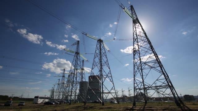 Electricity pylons carry power lines past cooling towers at the Novovoronezh NPP2 nuclear power station operated by OAO Rosenergoatom a unit of...