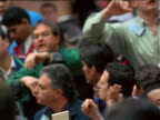 Electronic stock prices sign / tilt down + tilt up traders shouting + waving arms / Commoditites Exchange, NYC