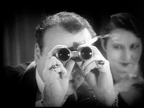 CU, ZI, B&W, Elegant couple at cafe table, man looking through binoculars, 1920's