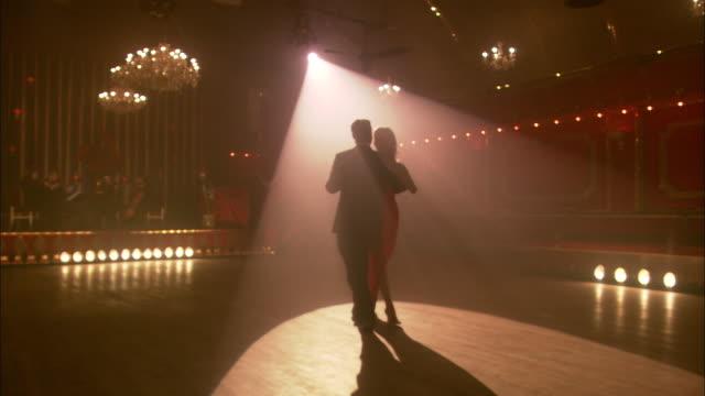 WS, PAN, Elegant couple dancing in ballroom, string quartet in background, London, England