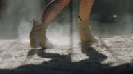 CU SLO MO. Elegant woman dances in boots on dusty barn floor.