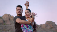 SLO MO. Elegant woman dances with partner and casts hand in front of camera in rocky desert terrain.