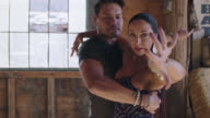 MED CU SLO MO. Elegant woman stares at camera and gestures with hand as she dances with partner in rustic setting.