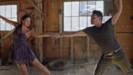 SLO MO. Elegant woman twirls and falls into the arms of her dance partner in rustic barn.