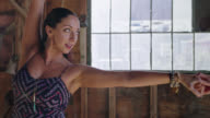 MED SLO MO. Elegant woman twirls into the arms of her ballroom dance partner in rustic wooden barn.