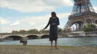Elegant Woman Walking Her Dog By The Riverside