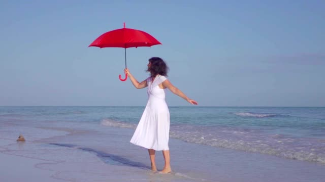Elegante donna che cammina con l'ombrello rosso In abito bianco sulla spiaggia