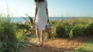 TS WS Elegant woman walks along path towards the sea, rear view.