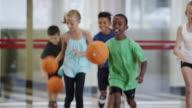 Bambini giocando a basket elementare in classe di educazione fisica