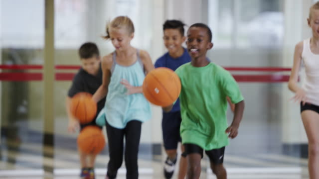 Elementary kids playing basketball during physical education class
