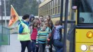 Elementary students getting onto schoolbus