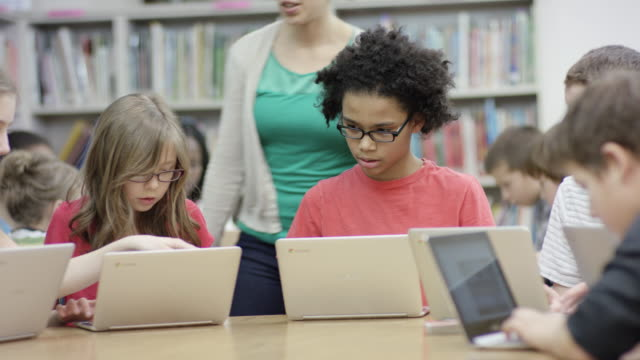 Elementary students working on computer laptops in library