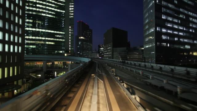 WS POV Elevated train moving through city at night / Tokyo, Japan