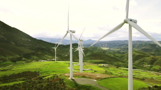 WS elevated view of wind turbines in motion with mountains / Ardales, Andalucia, Spain
