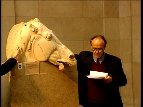 Elgin Marbles conference Sculpture of horse's head with Anderson standing next reading document Bas relief of man and horse Section of bas relief...