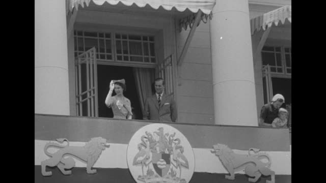 Elizabeth and Philip arrive at church greeted by priests and parishioners / royals wave from balcony of city hall standing over city flag seal and...