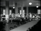 Ellis Island Immigration Center ALIEN'S DINING HALL WS Communal dining room w/ porters cleaning tables FG people eating BG MS Immigrant mural painted...