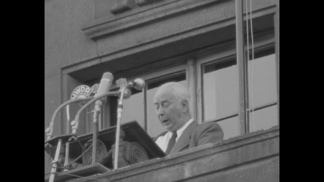 VS Elly HeussKnapp Theodor Heuss on balcony speaking to microphones / VS large crowd / German flag / metal bust / view of Heuss with large cast on arm