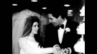 Elvis Presley and Priscilla after their wedding / they cut the cake and look adoringly at each other / photographers taking pictures of the couple /...