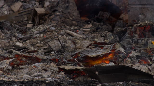 Embers burning underneath a layer of ash amid the rubble of a house fire