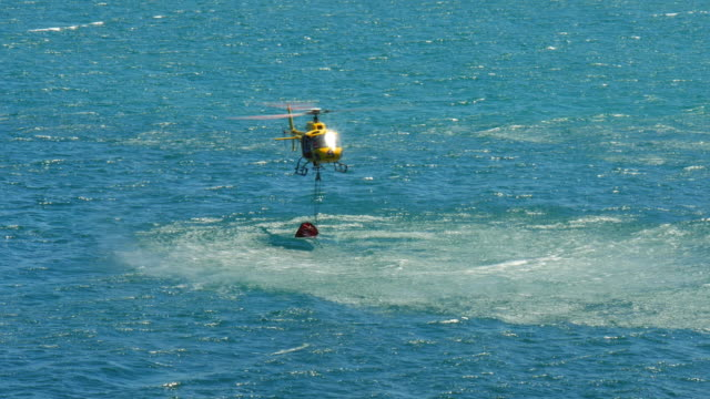 Emergency fire fighting helicopter collecting water from the sea