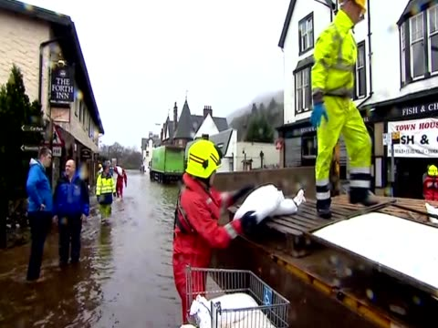 Emergency teams carry sandbags to deal with flooding in Scotland