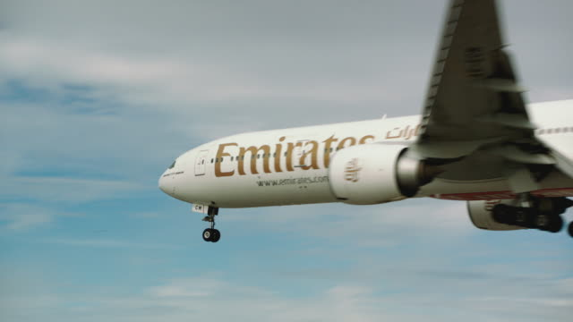 Emirates jumbo jet enters frame close-up on approach, then touches down for landing at SFO