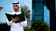 Emirati businessman checking folder documents