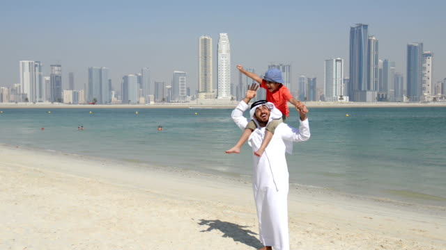 Emirati father and son on the beach