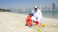 Emirati grandfather and little boy playing on the beach