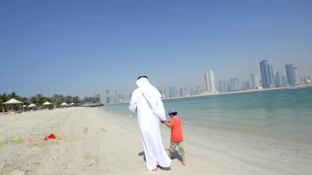 STEADICAM: Emirati grandfather and little boy walking on the beach