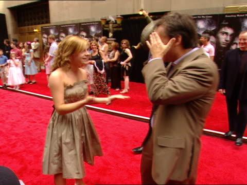 PREMIERE * Emma Watson standing on red carpet near Radio City Music Hall people press around hugging Chris Columbus talking catching up
