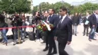 Emmanuel Macron lays flowers at a monument for Armenian priest Komitas in a ceremony marking the Armenian genocide in Paris