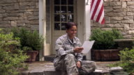 Emotional African American soldier reading love letter on front stoop