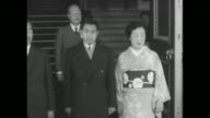 Emperor Hirohito Crown Prince Akihito and Empress Nagako wearing kimono descend staircase Akihito and Nagako return bow to bowing women / Hirohito...