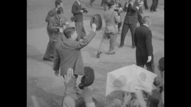 Emperor Hirohito gets out of car in village center waves his hat to crowd waving paper flags / WS he climbs steps to raised platform in middle of...