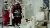 Emperor Trajan sitting on throne looking at scroll document and speaking with civil servants RECREATION Emperor Trajan in Ancient Rome on January 01...
