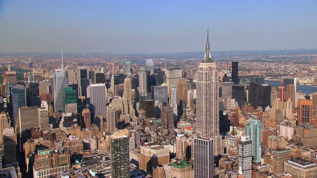 AERIAL Empire State Building amongst skyscrapers and buildings, and the upper stories and the radio antenna on top / New York City, New York, United States