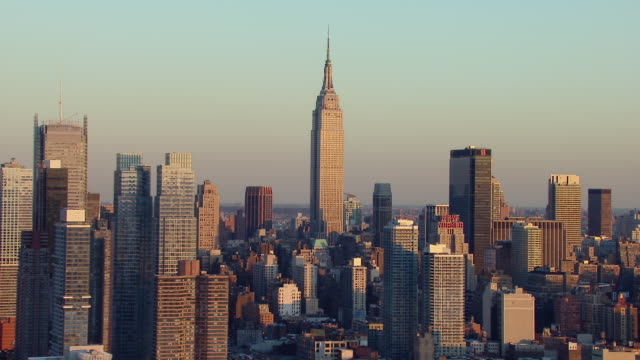 Empire State Building rises above the Manhattan skyline at golden hour in New York City.