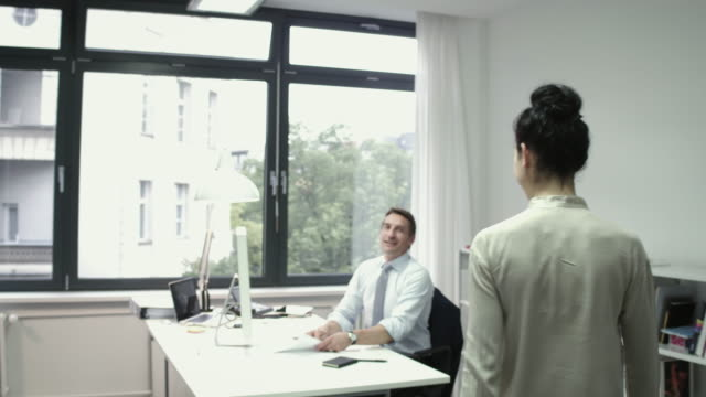 employee approaching manager in his office, shaking hands and discussing