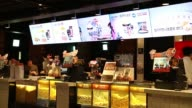 A employee assists customers at a snack bar at the CJ CGV Co Yeouido branch movie theater in Seoul South Korea on Wednesday May 25 Customers line up...