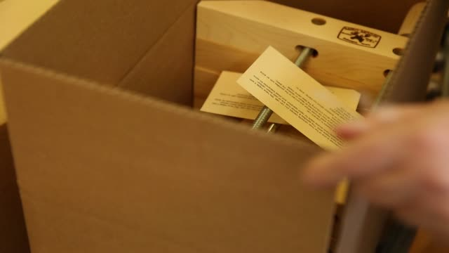 Employee places specialty clamps into boxes for instrument manufacturers at Dubuque Clamp Works in Dubuque Iowa August 8 2017 Shots CU of machine...