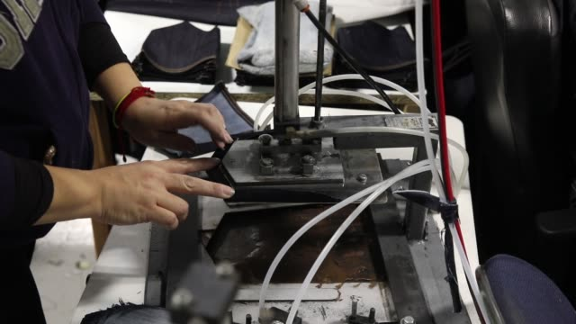 Employees add zippers and belt loops to jeans during manufacturing at Dearborn Denim in Chicago Illinois November 8 2017 Photographer Jim Young Shots...