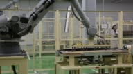 Employees and robotic machines move and organize solar panels such as the photovoltaic module HIT™ on the production line at the Panasonic Corp Eco...