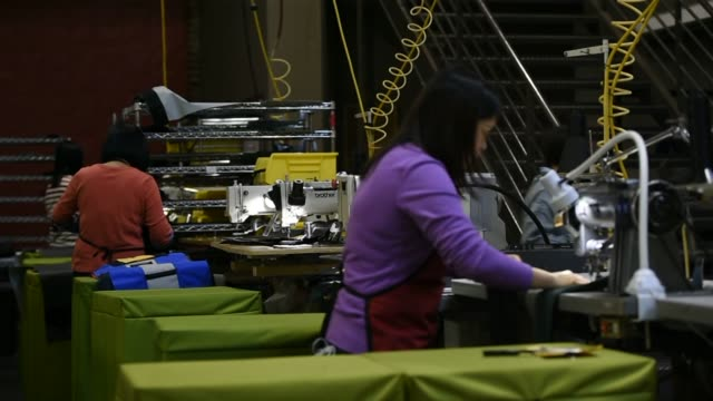 Employees assemble luggage and bags at the Timbuk2 headquarters in San Francisco California US Shots focus on seamstresses using sewing machines to...