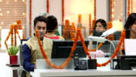 Employees in traditional dress working in the office, Delhi, India